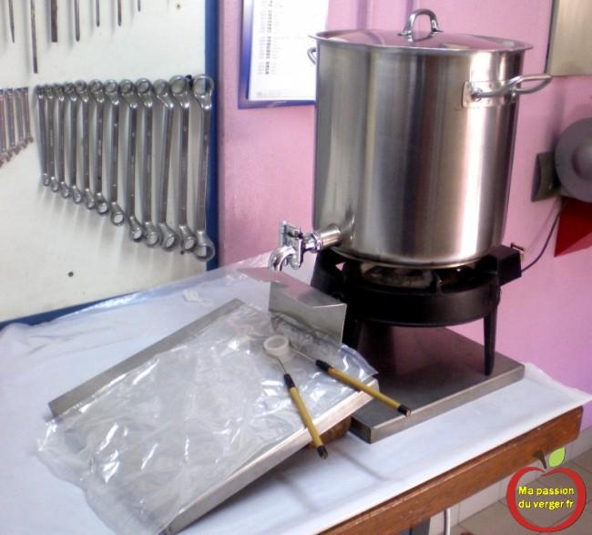 Une marmite en inox de 25 litres avec un robinet, un réchaud à gaz et des poches de bag in box 5 litres