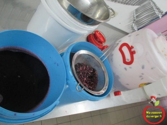 Faire passer le marc de raisin dans un passoire, sur un seau.