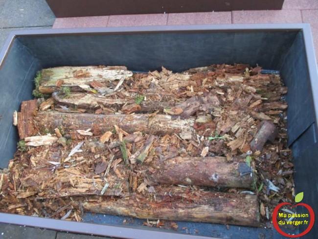 Dans chaque bac du potager sureleve, j'ai mis une couche de 15 cm à 20 cm de bois.
